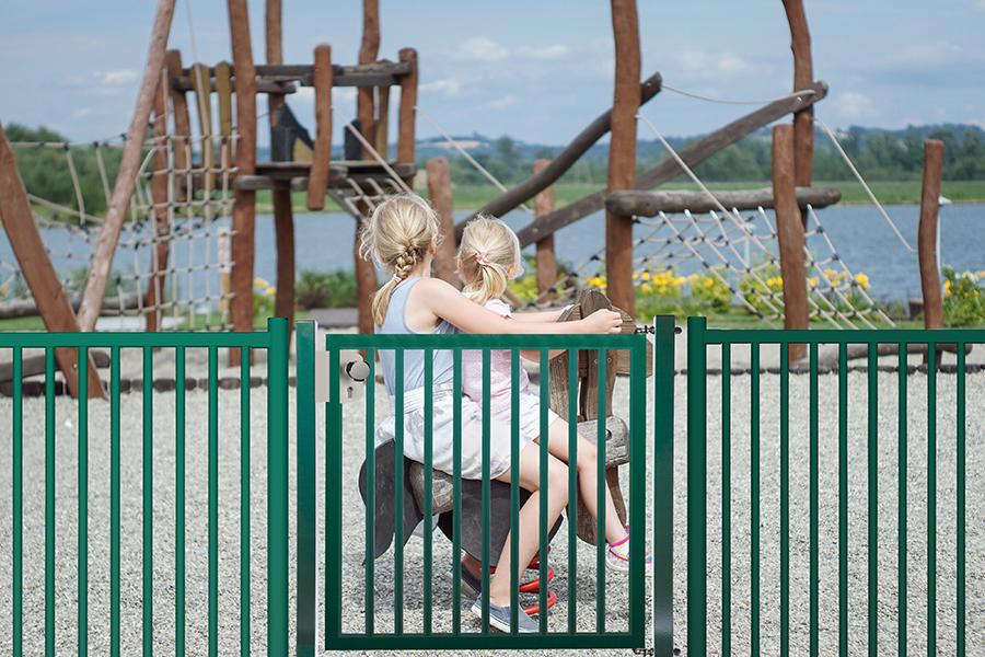 Puerta batiente Diabolo Plus de una hoja instalada en un parque infantil