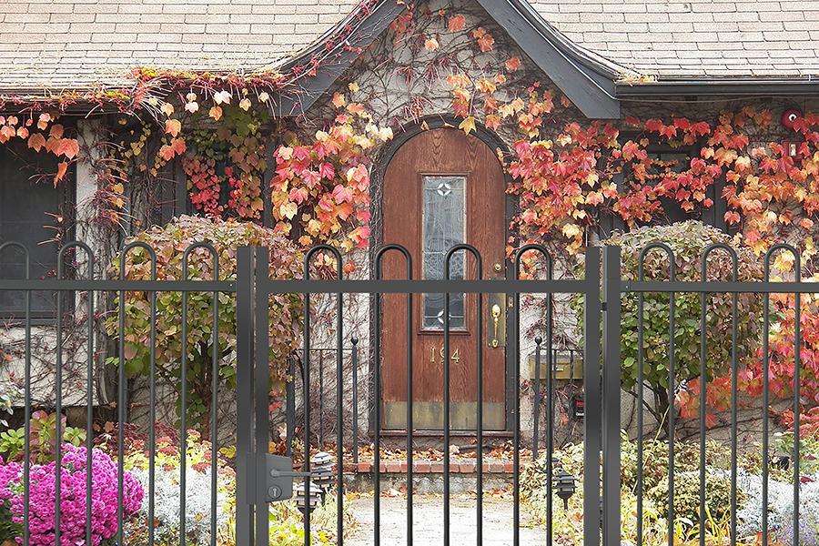 Puerta batiente Ondas Plus de una hoja instalada en una casa con fondo de otoño